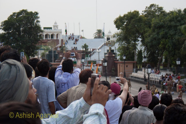 People using their cameras to record the flag lowering ceremony at the Wagah Border between India and Pakistan