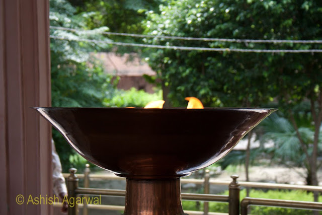 Urn with the memorial flame at the Jallianwala Bagh in Amritsar, garden in the background