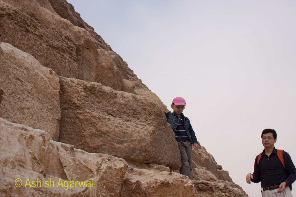 Cairo Pyramids - A tourist and his child posing on the stones of the Great Pyramid