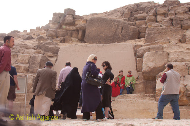 Cairo Pyramids - Tourists posing near the foot of the Great Pyramid, near a slab of rock