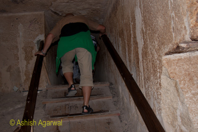 Cairo Pyramids - Tourist climbing out of the burial chamber of a small structure next to the Great Pyramid