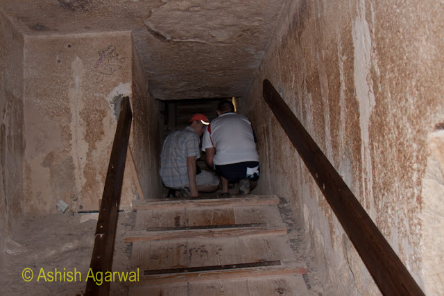Cairo Pyramids - Tourists crouched inside a burial chamber near the Great pyramid, apparently taking photos