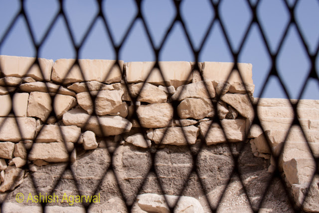 Cairo Pyramid - the stones of a structure next to the Pyramid, with the fence being blurred