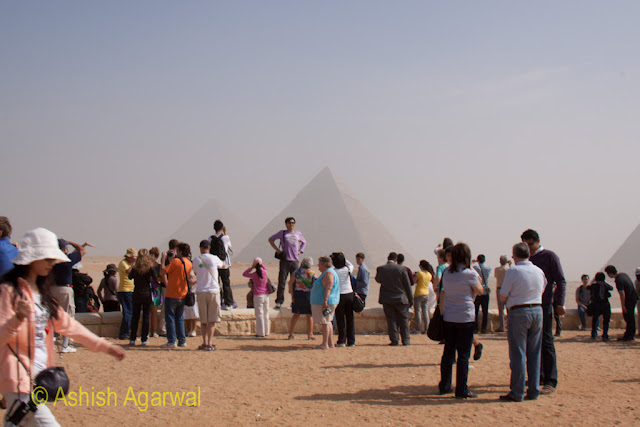 Cairo Pyramids - Tourists posing with the backdrop of the Great Pyramids at the Panorama Point in Giza, stock photo
