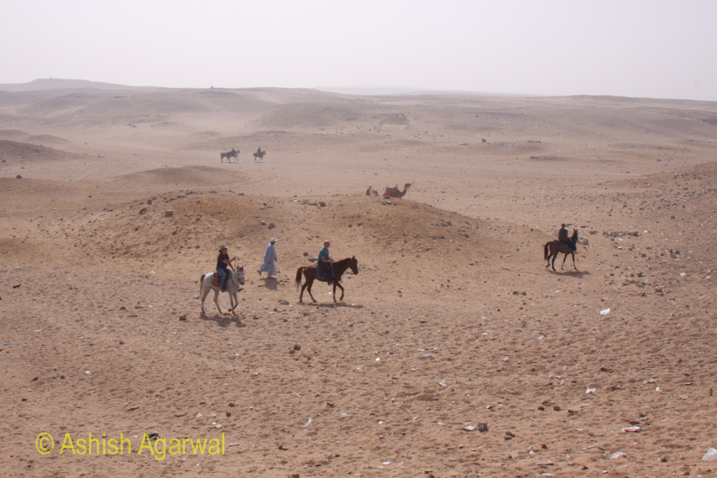 Giza Panorama Point - Tourists on horses and camels in the desert near the Pyramids in Cairo