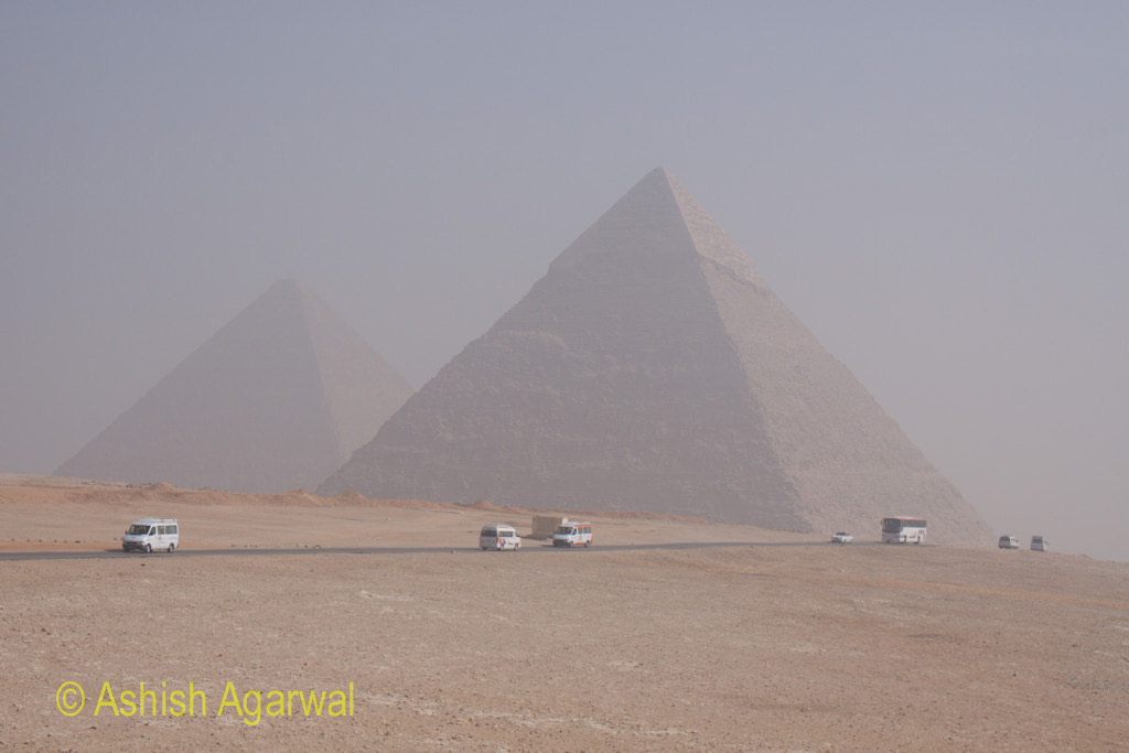 Cairo Pyramid - Panoramic view of Great Pyramids along with buses on the road