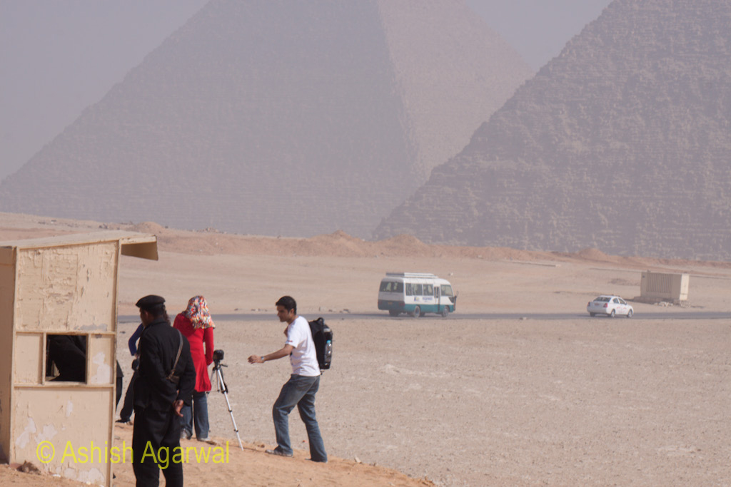 Security Outpost, and tourists with a tripod at the Great Pyramid in Giza