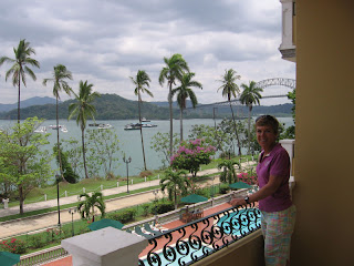 Nan on the balcony at Country Inn with Panama Canal and Balboa Yacht Club behind her