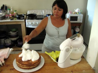 Paula starting to frost her tres leches cake