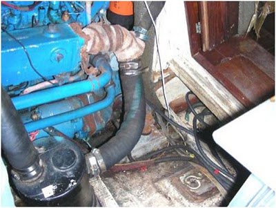Photograph of engine exhaust as seen from the starboard side, taken at the time of survey on 4/26/2010. The insulated piping is deteriorated, and there is minimal vertical separation between the point of seawater injection and the waterlift muffler.