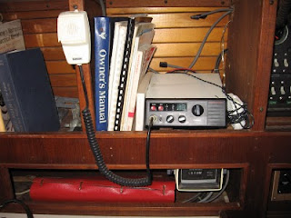 Shelf next to Uniflite electrical panel showing VHF radio (working) and engine hours meter (not working)