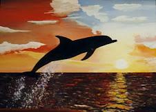 Delfín saltando sobre el agua con un atardecer de fondo