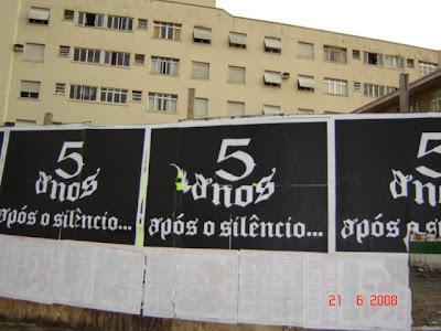 Cartaz em tapume de obra '5 Anos Pós o Silêncio'