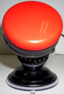 RJ Cooper switch poser. Image of a bright red push button mounted by velcro onto an angle-poise mount fixed by a rubber sucker foot.