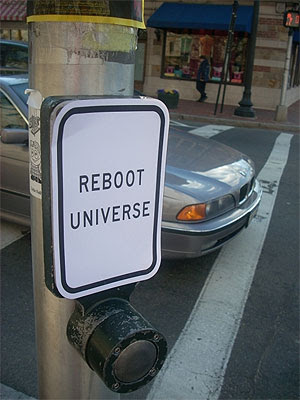 Image of a piece of street furniture with a heavy duty push button on a post. Above it are the instructions 'Reboot Universe'.