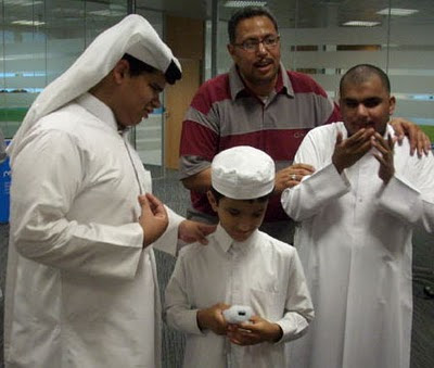 Image of three young blind males, in Quatari national dress, of smart white clothing and head-wear. The smallest holds a Wii remote, grinning a little, whilst taking instructions for an older peer.