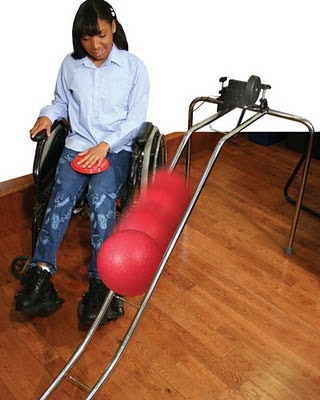 Image of a young woman to the side of a ramp, pressing an accessibility switch on her lap, triggering a switch activated bowling ball kicker.