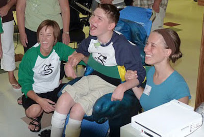Image of a young lad beaming brightly whilst playing a Wii Ski game using a chair controller. Flanked by two helpers who are also smiling broadly.