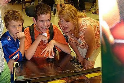 Image of a young man beaming, flanked by two on-lookers, whilst he plays an adapted pinball machine using a single accessibility switch.