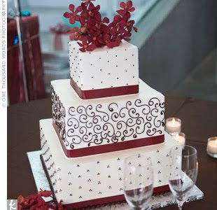 the three tiered cake had two flavors triple chocolate and white chocolate raspberry it featured intricate scrollwork red ribbons on each tier