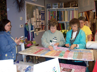 Quilters choosing their strips of fabric with Stacy's help