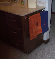 Blue and orange towels in bathroom with an old English D embroidered on them