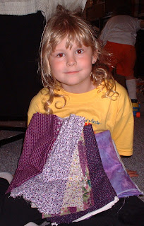 Abby at 8 with purple fabrics for her first quilt