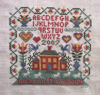 cross stitched house sampler