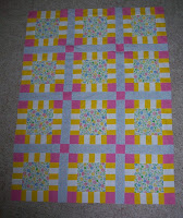 pink, yellow, blue and white charity quilt