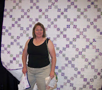 Pam in front of a purple and white nine patch quilt that she made for her sister