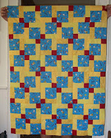 Disappearing Nine Patch quilt top using blue Snoopy fabric and assortment of yellows