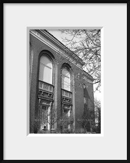 A black and white photo of a stately brick building with ornate scrolled stone work and tall arched windows could be found on any college campus.