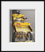 Framed photo of a child's bright yellow antique wagon on drab sidewalk