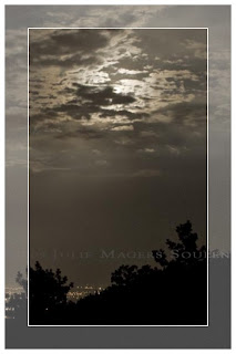 A framed sepia print of the full moon rising over the silhouette of the Rocky Mountains in Colorado.