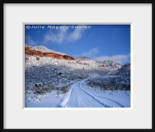 A framed photo of a narrow mountain road disappears up into the Rocky Mountains of northern Colorado on a winter day after the road has been freshly plowed.