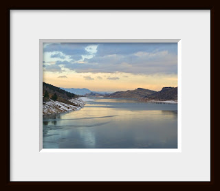 Framed photo of the approaching evening of a cold winter day paints the frozen Rocky Mountain lake in the subtle tones of a peach and pink alpine glow.