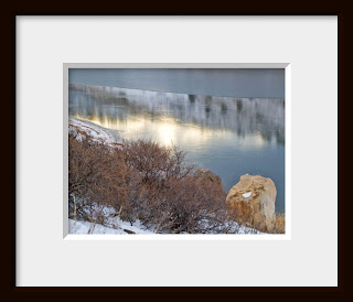 A framed photo of a hillside covered in Mountain Mahogany drops steeply to an ice covered lake reflecting the setting sun.
