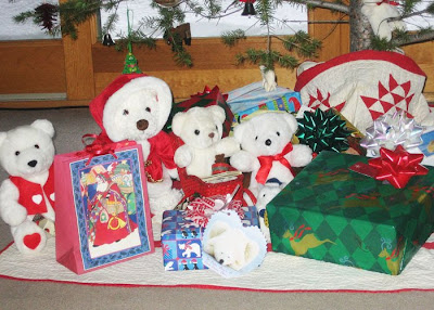 A family of white plush Christmas bears lives under a holiday tree.