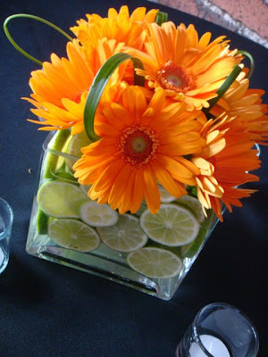 Third cube vases filled with sliced limes bright orange gerber daisies