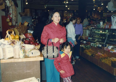 An Asian woman and her young daughter pose at a store counter.