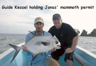 Photo of Mango Creek Lodge guide Kessel, holding a permit, and guest Jonas