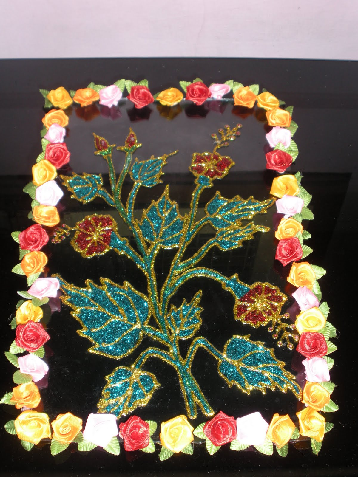 In this type of glass painting instead of glass black out liner 3d glitter out liner have been used also small rose flower have been used for the frame