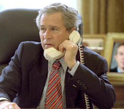 A photograph of George W. Bush in the White House cradling a phone upside-down to his ear