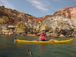 Marie paddling past vividly coloured cliffs - a real visual symphony!