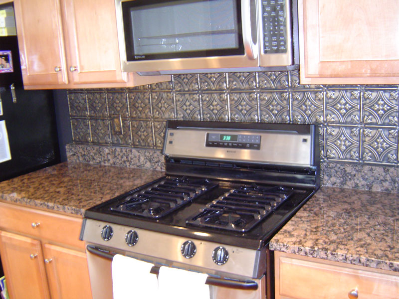 The faux tin backsplash is an easy and relatively inexpensive kitchen