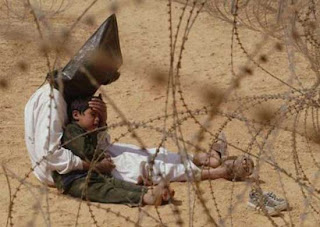 "This picture of a detained ""Iraqi"" with his 4-year-old son was taken near Najaf, ""Iraq,"" on March 31, 2003. It was selected as World Press Photo of the Year for 2003. The photographer was Jean-Marc Bouju of the Associated Press."