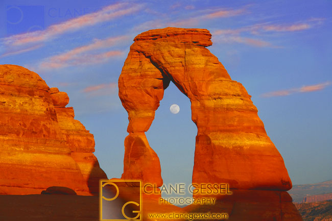 the full moon rising through delicate arch in arches national park, utah