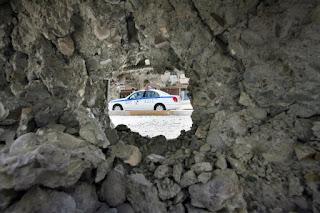 Un vehículo de la policía iraquí visto a través de un agujero en un muro provocado por uno de los atentados. AFP