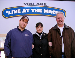 Soo Theatre Project Board President Dianna George celebrates the transfer of the Mackinaw Crossings Theater equipment donation  from Jim Wehr, owner and manager of Mackinaw Crossings (right). Fred Schmidt, Wehr's operations manager, is on the left. Photo by Meta Geyer.