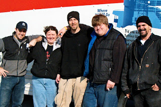 The Mackinaw Theater crew carefully dismantled and labeled all of the curtains and drops, lighting and sound equipment, and stage rigging.  Caught on a rare sunny day during the move were (L-R): Patrick West, sound; Rachel Love, stage manager; Steve Klunder, lighting; and crew members Jake George and Bob Green.  Photo by Liz Brugman.